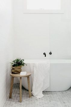 Mur blanc, sol gris, robinetterie noire, bois et plantes