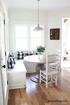 Ten June: A Farmhouse, Buffalo Check Built in Breakfast Nook white painted built in benches, windows, light hardwood floors, round rustic wooden table, vintage painted white ladder back chairs, black and white buffalo check/plaid pillows