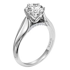 Art Carved - Diamond solitare engagement ring with round center stone set in a tulip setting with open pave side diamond detail.