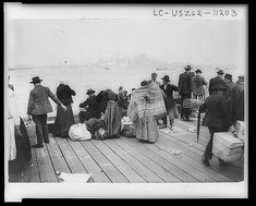 Immigrants on the Deck of a Ship entering the harbor in New York after sailing on a ship for weeks. In the distance you can see tall buildings of New York. late 1800s