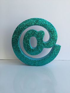 """Self standing """"@"""" with glitter. Measures approx 9.5"""" in diameter. Made from a heavy cardboard and will stand on it's own. *If you are using this outdoors where it is windy, I recommend leaning it against something to avoid it from blowing over)  *This listing comes with the front face covered in glitter. It's then sealed with a clear coat to keep your glitter from falling off! :) You can refer to our color chart in the photos to help with your color selection."""