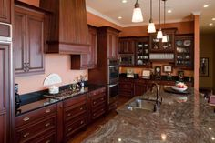 Orange walls add warmth to this traditional kitchen, complimented by expansive wood cabinetry. Check it out at HGTV.com.