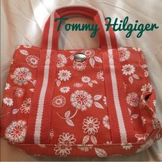 Orange with flowers Tommy Hilfiger bag Small Tommy Hill figure bag orange with white flowers, zipper inside hideaway, and great condition. 8 inches long 10 inches wide Tommy Hilfiger Bags Mini Bags
