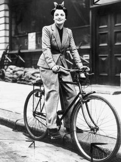 Young woman on a bicycle, wearing a trouser suit, 27 Oct 1939.  With the increase in the popularity of cycling owing to petrol rationing, dressmakers and tailors set out to make suitable clothes for it. Aquascutum of London produced a 3-piece tailored suit in Scutum cloth which is rainproof and windproof. The 3-piece consists of a coat, a skirt with three inverted pleats in front, and a pair of trousers zipped at the sides. So a girl can ride to work in trousers and then change into a skirt…