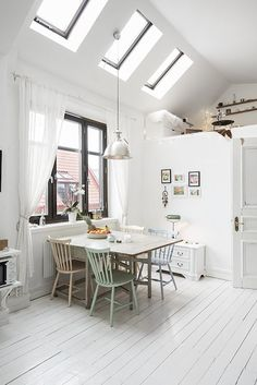 White kitchen with pastel accents in a charming one room Swedish apartment