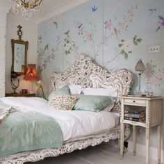 Delicious carved wood details this ornate bed frame. Victorian lampshade and floral wall mural.   Decidedly Feminine and Romantic Bedroom Decorating Ideas