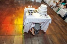 Kids playing hide and seek under the wedding cake in Thessaloniki, Greece. Wedding reportage photography