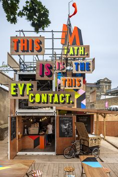 The Movement Café, Greenwich - Designer Morag Myerscough added more than a splash of colour to the site by fixing painted wooden boards to the upper scaffolding structure carrying the words of a poem-tweet by Olympic bard Lemn Sissay