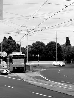 L1M2AS3. Tv Mode.  SHARP FOREGROUND BLURRED MOTION BACKGROUND. 1sec, f/9, 70mm, ISO 100. Taken outdoors, tripod, ND filter as it was midday. Focus is on tram in the foreground crispy and sharp, while the white car on the bacground was captured with blurred motion. Leading lines above the tram by cable guiding to tram, while road lines guide the viewer to both tram and car.