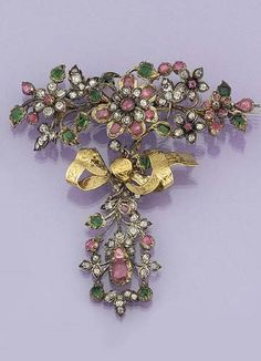 An 18th Century Diamond, Foiled Emerald, and Ruby Brooch. In the Form of a Floral Spray with Central Diamond and Ruby Flower Head Cluster Surrounded by Smaller Fflower Heads and Foiled Emerald Leaf Detail, the Stem with Foliate Engraved Ribbon Bow Suspending a Matching Diamond, Ruby, and Emerald Cluster Pendant Drop.