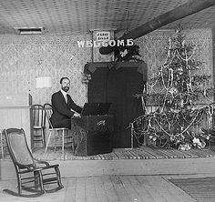 "https://flic.kr/p/dVT955 | Christmas Reed Organ Concert | Gentleman seated at folding reed organ located on stage with a decorated Christmas tree.  The signs read ""Jesus Saves"" and ""Welcome."""