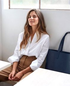 An effortless work look to try now: crisp, white button-down shirt, a classic tote bag, and high-waisted camel pants.