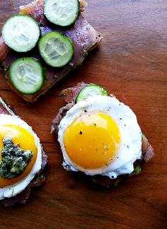 taking avocado toast to the next level! avocado toast with sliced cucumber, smoked salmon, topped with a fried egg and finished with pesto