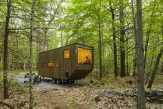 Angular tiny house with big picture windows in the woods.