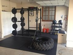 Cool strength training gym with a trailer tire for crossfit exercises and free weights on a power rack