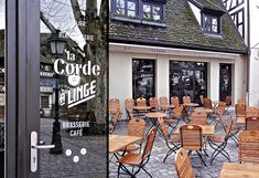 White text on windows, warm cafe seating outside. Again, black trim