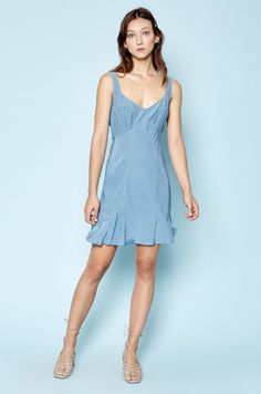 """Meet the summer mini of your dreams. A fitted top, gradually relaxing into a slight A-line with gentle ruffles. An open neck + flattering silhouette make this dress a warm weather essential.  Style Details:  100% organic rayon Bra friendly Gentle shirring at bust accommodates a variety of bust sizes Valentina is 5'9 + wearing a size small Dry Clean Only   How It's Made:  About this print: """"Denim Ditsy"""" was designed in house + printed locally in Los Angeles Designed by..."""