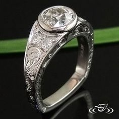 Custom cast platinum engagement ring with a 1.32 carat European cut diamond bezel set with 2 bead set 2.3mm old cut diamonds on either side. Scroll engraving on top of the band with 2 filigree curls in side panels. Half wheat engraving on sides.