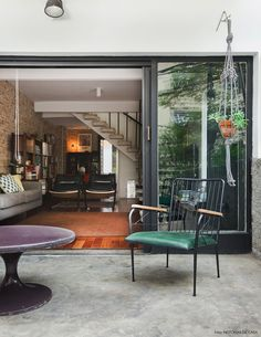 pátio externo com piso de cimento queimado, móveis antigos e suporte de macramê para vasos de plantas