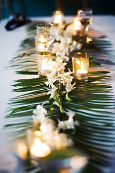 Simple but very elegant orchid runner.  Palm fronds laid down the center of the table with dendrobium orchids laid on top.  You could do it in any of the colors that dendrobium orchids come in naturally- white, green or purple would be beautiful! PERFECT
