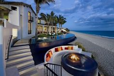 tropical, on the beach, palm trees, infinity pool, and outside seating...um Yes please!