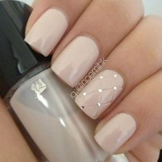 "This is another very simple look. The nails are painted a nude color and the ring finger is given a ""quilted"" look. Where the points come together, tiny rhinestones are added for just a small amount of bling. This one is girly and very pretty."