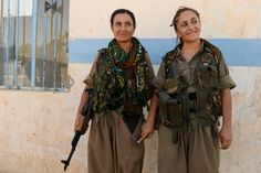 Felice Budak, 24, left, and Zekia Karhan, 26, react to a bit of friendly ribbing from a couple of fellow male fighters while posing for a portrait in Makhmur, Iraq, on Aug. 23, 2014. Karhan and Budak are guerrillas in the Kurdistan Workers' Party. Joshua L. DeMotts / Stars and Stripes