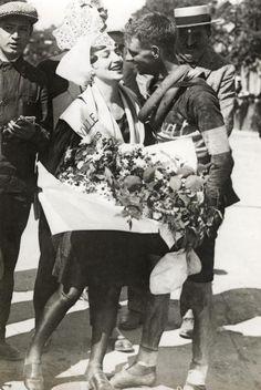 1928 22/6 rit 6 Les Sables-d'Olonne > De Australiër Hubert Opperman ontvangt na zijn aankomst bloemen en kussen van het mooiste meisje uit Sables/Kisses and flowers from the local beauty for Hubert Opperman
