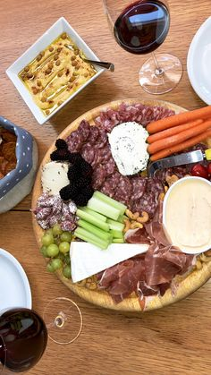 Plate with cheese, meat, hummus, vedgetables, nuts and fruits.