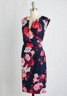 Give a toast to your fellow professors in this sophisticated navy dress. This feminine number flaunts a magenta, maroon, and white floral print layered atop its blossom-textured woven silhouette. Side-swept with pleats that match its notched neckline, this sheath is a wonderful wear.