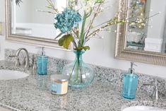 tallish arrangements in pretty glass vase between mirrors