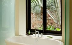 This master bathroom's soaking tub sits beneath a large window looking out into a private yard surrounded by a stone wall and shaded by palms. On either side of the tub are frosted glass panes meant to keep any splashes contained. Small Bathroom Window, Bathroom Window Glass, Bathroom Windows, Bathroom Decor, Bathroom Remodel Master, Bathroom Window Treatments, Bathroom Renovations, Luxury Master Bathrooms, Window Glass Design