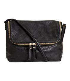 Schwarz. Handtasche aus geprägtem Lederimitat. Die Tasche hat einen Überschlag mit Reißverschluss und einen schmalen, verstellbaren Schulterriemen. Ein