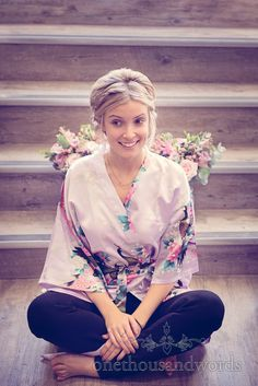 Beautiful blonde bridesmaid in silk kimono peacock design dressing gown with floral wings. Photography by one thousand words wedding photographers