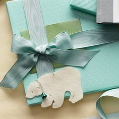 This felt animal makes a fanciful gift topper. Choose from a polar bear, cat, seal, wolf, mouse, fish, or bear.Get the templates for them. Silk Moire ribbon (#20001), Color #23, Width #25; mokubany.com. Aqua Matelasse Wrap, bellocchio.com.