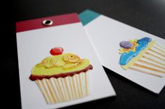 For each tag, I stuck two old business cards together, printed sides in. I cut out the cupcakes from a disposable paper placemat and used Sakura 3D crystal lacquer for surface interest. Finished off each tage with a strip of washi tape and an eyelet.