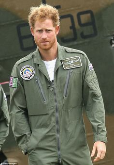 Prince Harry walks on the airfield at Goodwood Aerodrome as he is shown a Spitfire Aircraf...