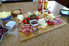 My go-to appetizer to serve guests for happy hour: a cheese board filled with different cheeses, meats, fruits, and extra goodies. Yum!