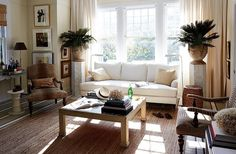 "William's favorite spot is the serene living room, which is flooded with light in the morning. ""My dog, Baylor, and I usually sit in there on the sofa, and I check emails and drink my coffee,"" he says. A braided jute rug defines the seating area and separates it from the dining area. William often rolls up the rug and paints canvases on the striped floor."