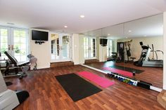 """Basement Floor. Lowering the basement slab also allowed for a spacious workout room. A mirror wall helps make it feel much larger. """"Cushion Step"""" vinyl flooring really stands out and is very funcational. We also added French doors to the outside paver driveway. They"""