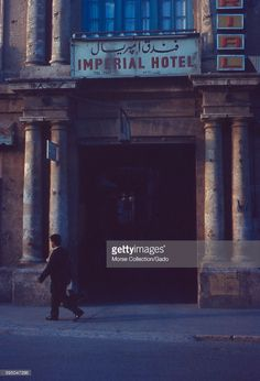 View of an Arab man walking past the entrance to the Imperial Hotel, located in East Jerusalem, Israel, just inside the Jaffa Gate of the Old City, November, 1967. A sign in Arabic and English advertises the hotel and its telephone number. Bullet hole damage is visible on the building's facade. (Photo by Morse Collection/Gado/Getty Images).