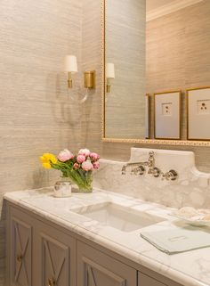 Simple painted molding frame around mirror, custome shaped backsplash, pretty wall paper, sconce, cabinets.