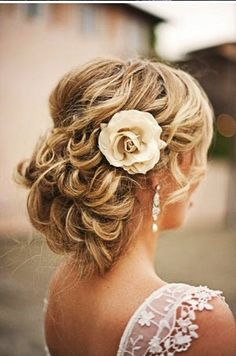 Curled low updo for wedding hair - add a flower for a touch of whimsy #bridal #hairstyles #weddinghair #wedding