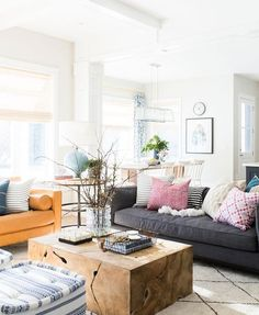 eclectic living room with natural wood block table, dark gray sofa, and pops of pink