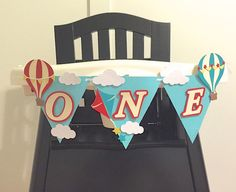 Up, Up, and Away someones turning one today! First Birthdays are so special! Lets celebrate your little ones first birthday with this ONE high chair banner. ****listing is for highchair banner only****  Banner features hot air balloon, kite and clouds made from premium quality card stock and reads ONE with each letter slightly elevated off the paper for a multidimensional look. It is all strung together on pretty white ribbon.  Size: Each pennant measure approx. 5 x 4.5   Perfect decoration…