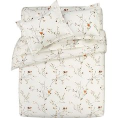 Sakura Bed Linens I A botanical pigment print in burnt oranges, greens and rust with brown branches is scattered across a soft white background. Reversible cotton duvet cover and flanged pillow shams have flap closures