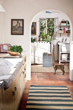Model Carolyn Murphy's Los Angeles kitchen feels more Marseille than Malibu. The marble farm sink, the terra-cotta tiles, even the cat all bring to mind a French country farmhouse.
