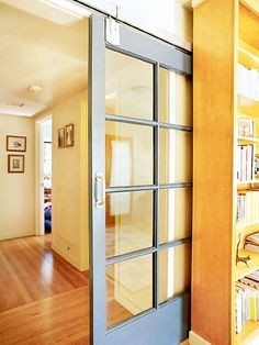 Porte coulissante à vitrages avec croisillons. La porte est posée en applique mais une étagère la camoufle lorsqu'elle est ouverte, on peut ainsi penser qu'il s'agit d'une porte à galandage.