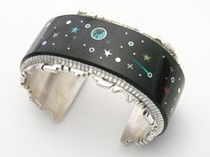 "Cuff | Alvin Yellowhorse. (Navajo) ""Night Sky"". Sterling silver with mosaic inlay design depicting a ""Night Sky"" with Comets, Moons, Planets, and Stars using Black Jade, Turquoise, Coral, Lapis, and Opal for the Comet's Tail."