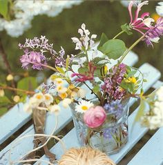 Pretty jam jar filled with hand picked wild flowers on a gorgeous duck egg blue French cafe style chair